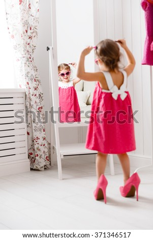 little girl child fashionista looking in the mirror at home in a pink dress, shoes and sunglasses - stock photo