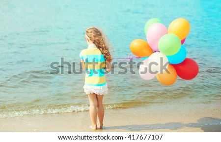 Little girl child with colorful balloons standing on beach over sea view back - stock photo