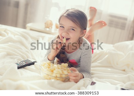 Little girl child with sna?ks and remote control watching tv set lying on bed in room. 6 years old child watching tv laying down on a white carpet at home alone. cute little girl  - stock photo