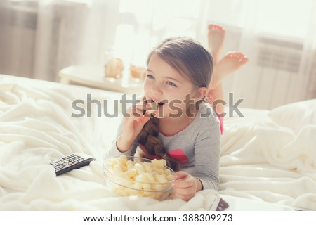 Little girl child with snacks and remote control watching tv set lying on bed in room. 6 years old child watching tv laying down on a white carpet at home alone. cute little girl  - stock photo