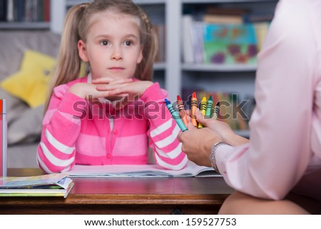 Little girl chooses the color pencils with hand psychologist - stock photo