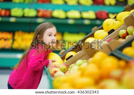 Little girl choosing a ripe melon in a food store or a supermarket - stock photo