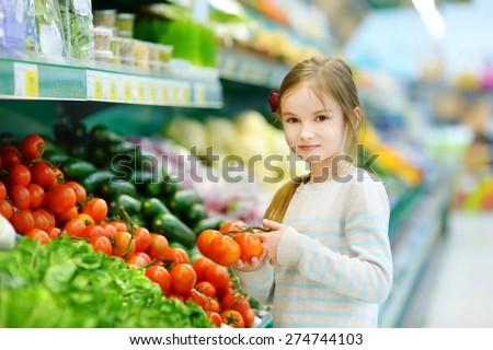Little girl choosing tomatoes in a food store or a supermarket - stock photo