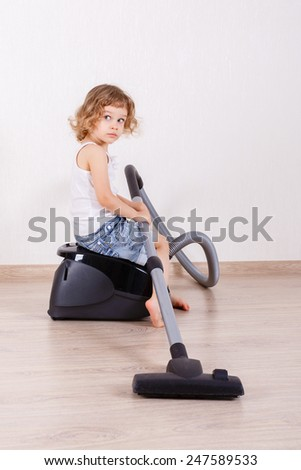 Little girl cleans the floor in the room with a vacuum cleaner.  Mother's helper. Housekeeping. - stock photo