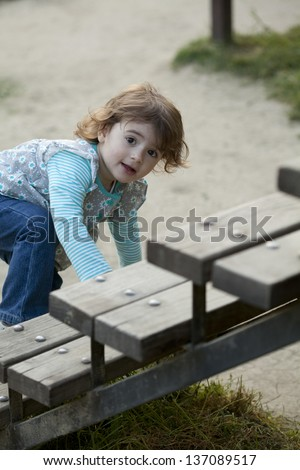 Little girl climbing on the stairs in the park - stock photo