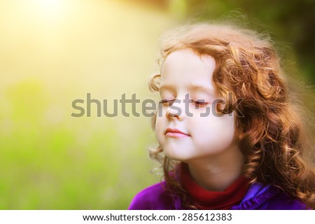 Little girl closed her eyes and breathes the fresh air in the park. - stock photo