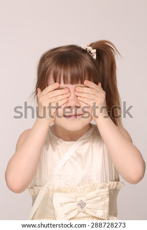 Little girl closed her eyes with hands. Girl with ponytail looking so funny. - stock photo