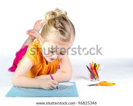 Little girl coloring a rainbow on white background - stock photo