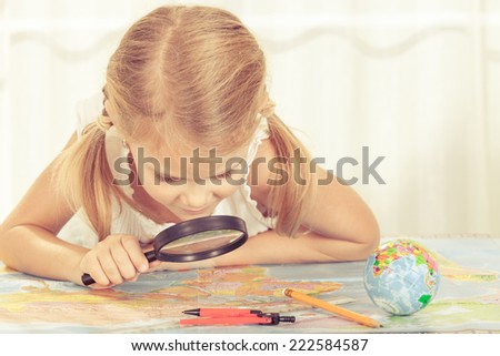 little girl considering a world map with a magnifying glass at home - stock photo