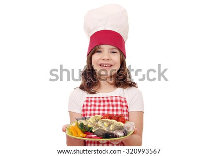 little girl cook with prepared trout fish on dish - stock photo
