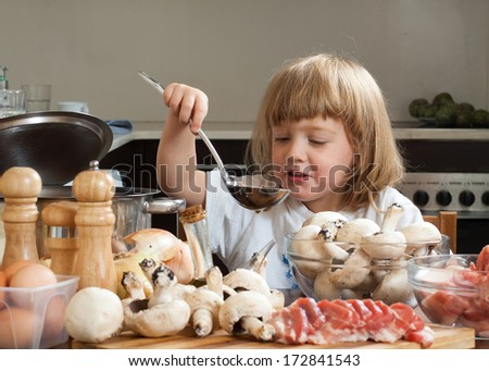 little girl cooking near kitchen table - stock photo