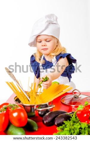 Little girl cooking soup - stock photo