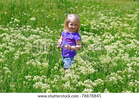 Little girl costs in a grass outdoors smiling - stock photo