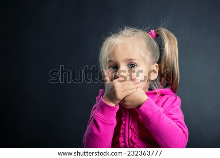 Little girl covers her mouth with hands - stock photo