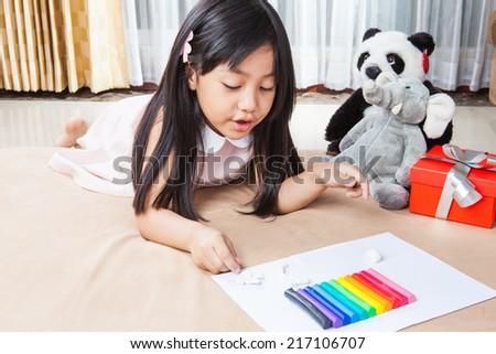 Little girl creating toys from playdough - stock photo