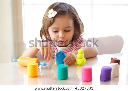 Little girl creating toys from playdough - stock photo