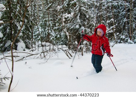 Little Girl Cross Country Skiing. Making a Ski Track. - stock photo