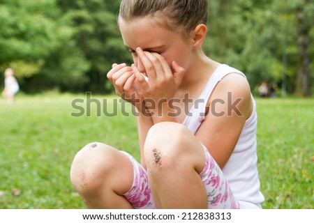 little girl crying because her knee hurts after falling down - stock photo
