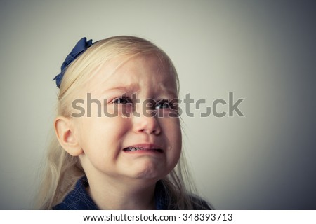 Little girl crying. Really upset. Tears on her cheek - stock photo