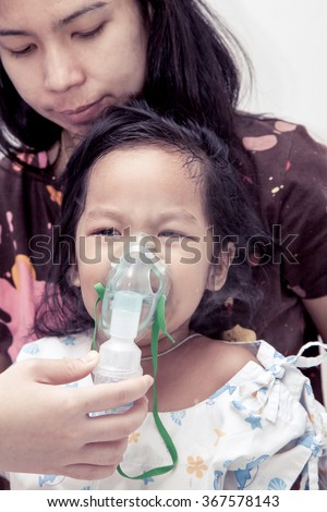little girl crying while getting in inhaler mask in hospital in vintage color tone - stock photo