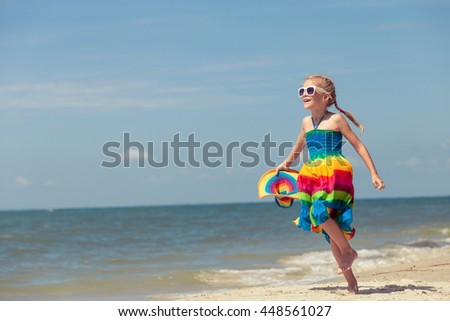 Little girl dancing on the beach at the day time. One kid having fun on the nature. Concept of happy life. - stock photo