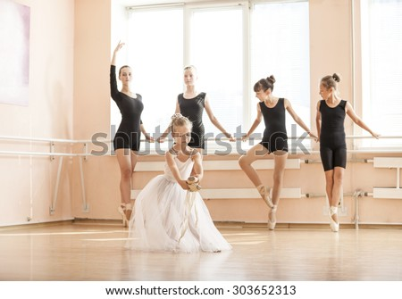 Little girl dancing with pointe shoes, older classmates warming up at the barres. At ballet dancing class. - stock photo