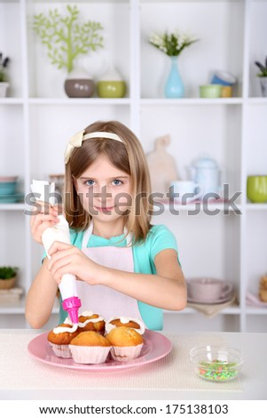 Little girl decorating cupcakes in kitchen at home - stock photo