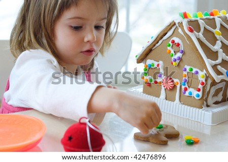 Little girl decorating gingerbread house for Christmas - stock photo