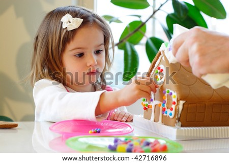 Little girl decorating gingerbread house with colorful candy for Christmas - stock photo
