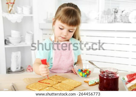 Little girl decorating prepared cookies in kitchen at home - stock photo