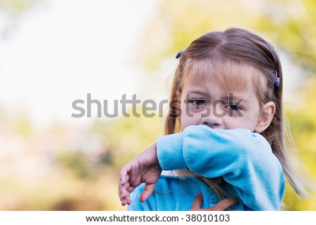 Little girl demonstrates coughing or sneezing into her elbow to avoid spreading unwanted germs. - stock photo