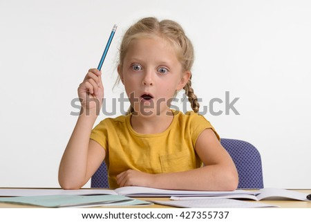 Little girl discovers the world and that is why she is very amazed by the new information she got. Opened mouth and big blue eyes show real amazement. Young girl holds a pencil in her hand. - stock photo