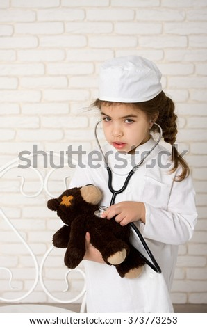 Little girl doctor in the white uniform with stethoscope and sick bear - stock photo