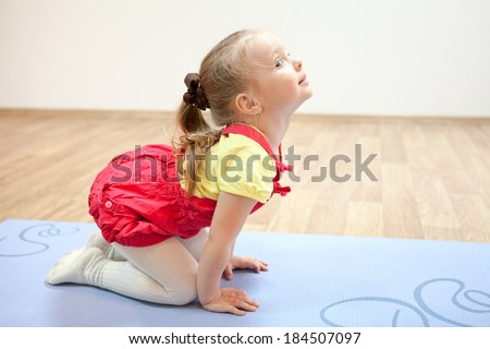 Little girl doing a yoga pose. - stock photo