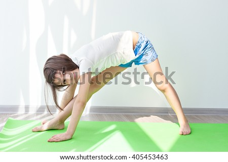 little girl doing gymnastics on a green mat for yoga. children's fitness, yoga for children. doing fitness exercise and stretching - stock photo