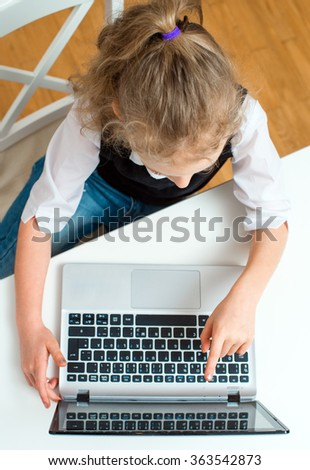 Little girl doing her homework at home, using laptop. Top view. - stock photo