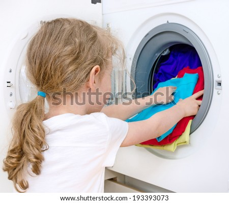 Little girl doing laundry. Housework concept. - stock photo