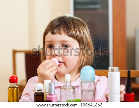 little girl doing makeup at the table - stock photo