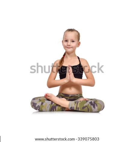 little girl doing namaste sitting on the floor in lotus position - stock photo