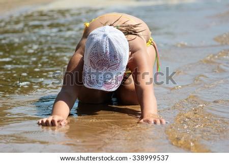 little girl doing yoga on the shore - stock photo