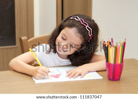 Little girl drawing a house with pencils - stock photo