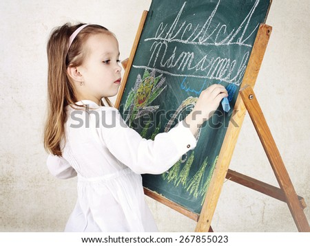 Little girl drawing a picture with chalk on the blackboard - stock photo