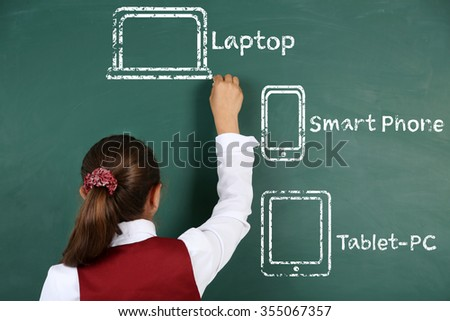 Little girl drawing different gadgets on the chalkboard - stock photo