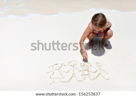 Little girl drawing family picture on a beach - stock photo