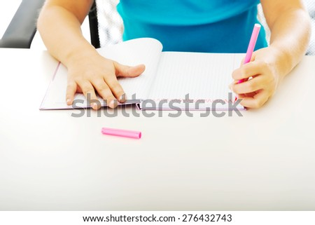 Little girl drawing in note using marker - stock photo