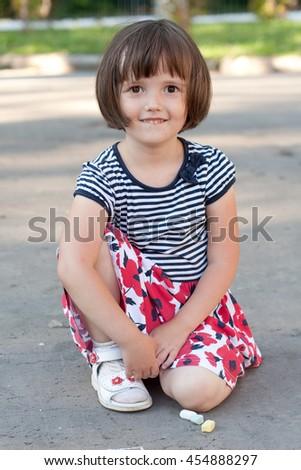 Little girl drawing on the asphalt - stock photo