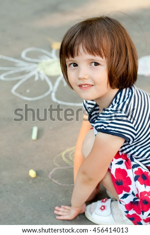 Little girl drawing on the asphalt close-up - stock photo