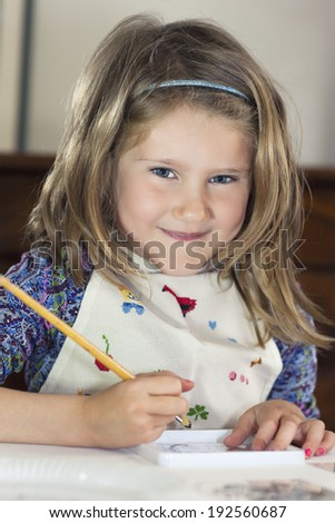 Little girl drawing paint at home - stock photo