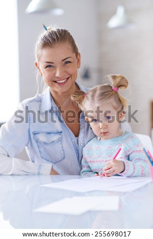 Little girl drawing with crayon while her mother looking at camera - stock photo