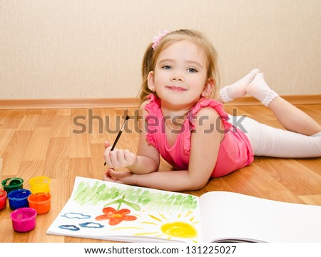 Little girl drawing with paint at home - stock photo